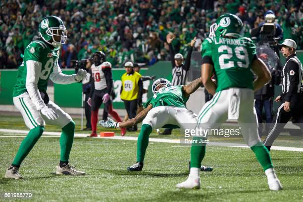 Kienan LaFrance celebrates with Caleb Holley and Duron Carter of the Saskatchewan Roughriders after at touchdown in the game between the Ottawa...