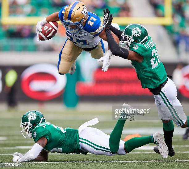 Kienan LaFrance of the Winnipeg Blue Bombers leaps over a diving Will Blackmon of the Saskatchewan Roughriders in the game between the Winnipeg Blue...