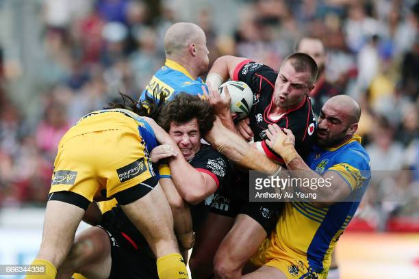 Kieran Foran and Charlie Gubb of the Warriors are tackled by Tepai Moeroa Beau Scott and Tim Mannah of the Eels during the round six NRL match...