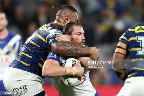 Kieran Foran of the Bulldogs is tackled by Junior Paulo of the Eels during the round 23 NRL match between the Parramatta Eels and the Canterbury...