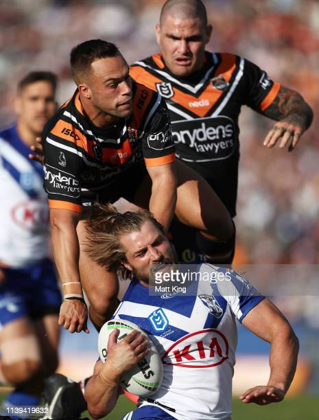 Kieran Foran of the Bulldogs is tackled by Luke Brooks of the Tigers during the round three NRL match between the Wests Tigers and the Canterbury...
