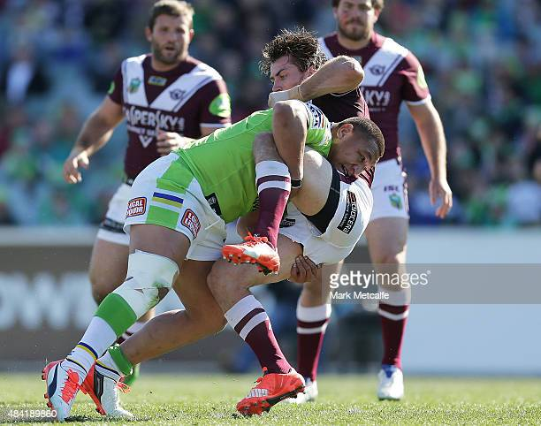 Kieran Foran of the Sea Eagles is tackled by Josh Papalii of the Raiders during the round 23 NRL match between the Canberra Raiders and the Manly...