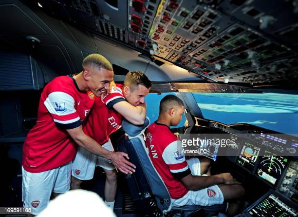 Kieran Gibbs Carl Jenkinson and Alex OxladeChamberlain of Arsenal sit in an Airline Simulator during the Arsenal Emirates Airline Simulator Challenge...
