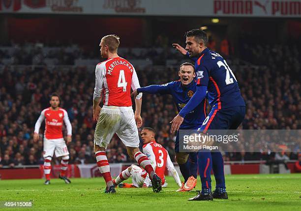 Kieran Gibbs of Arsenal scores an own goal to give Manchester United the lead as Wayne Rooney of Manchester United celebrates with Robin van Persie...