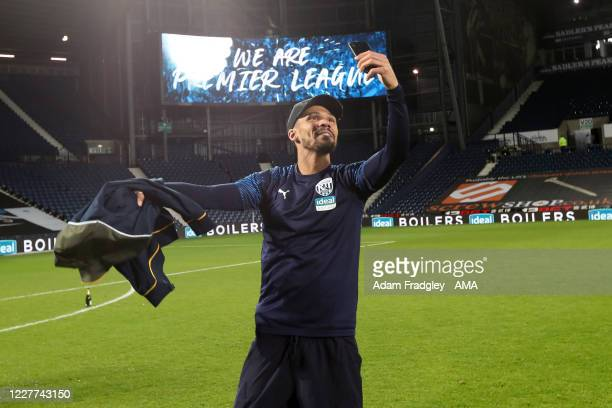 Kieran Gibbs of West Bromwich Albion takes a selfie as he celebrates promotion to the Premier League on the pitch at the end of the Sky Bet...