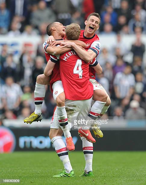 Kieran Gibbs Per Mertesacker and Laurent Koscielny celebrate celebrate the Arsenal victory after the Barclays Premier League match between Newcastle...