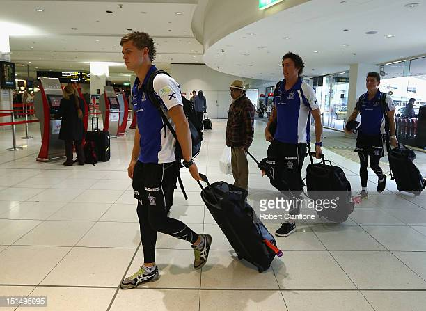 Kieran Harper Samuel Wright and Aaron Mullett of the North Melbourne Kangaroos arrive at Melbourne Airport on September 7 2012 in Melbourne Australia