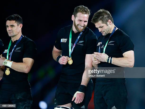 Kieran Read of New Zealand and Richie McCaw of New Zealand inspect their winning medals during the 2015 Rugby World Cup Final match between New...