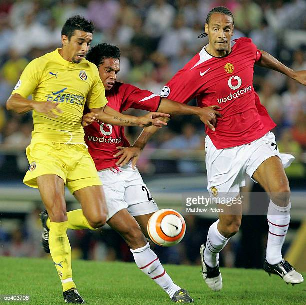 Kieran Richardson and Rio Ferdinand of Manchester United clash with Antonia Guayre of Villarreal during the UEFA Champions League match between...