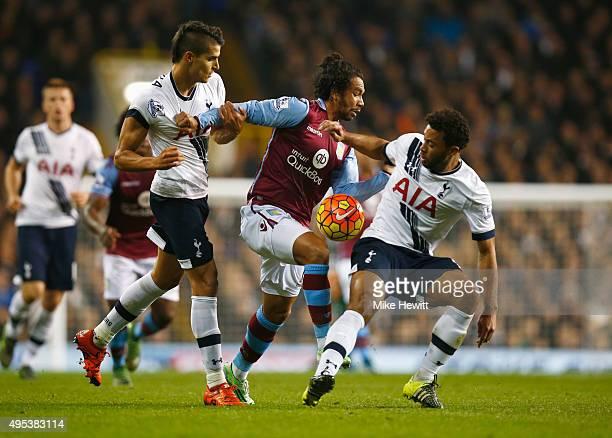 Kieran Richardson of Aston Villa goes between Erik Lamela and Mousa Dembele of Tottenham Hotspur during the Barclays Premier League match between...