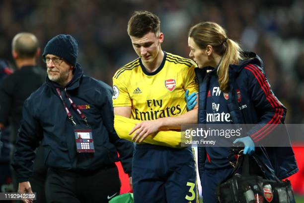 Kieran Tierney of Arsenal leaves the pitch following an injury during the Premier League match between West Ham United and Arsenal FC at London...