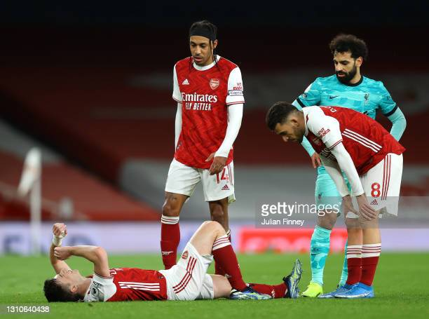 Kieran Tierney of Arsenal reacts after picking up an injury as teammates Pierre-Emerick Aubameyanga and Dani Ceballos and Mohamed Salah of Liverpool...