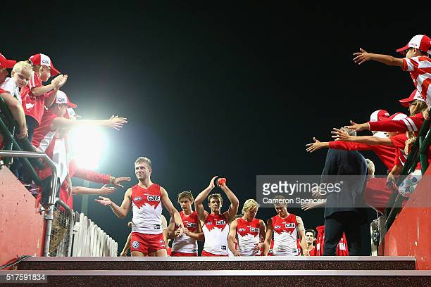 Kieren Jack of the Swans and team mates celebrate with fans after they head down their race after winning the round one AFL match between the Sydney...