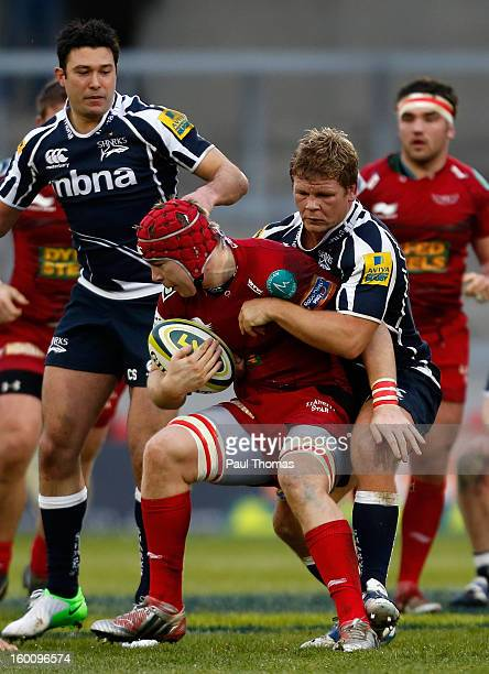 Kiernan Murphy of Scarlets is tackled by Daniel Braid of Sale Sharks during the LV= Cup match between Sale Sharks and Scarlets at Salford City...