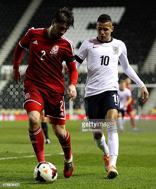 Kieron Freeman of Wales holds off pressure from Ravel Morrison of England during the U21 European Championship Qualifier between England and Wales at...