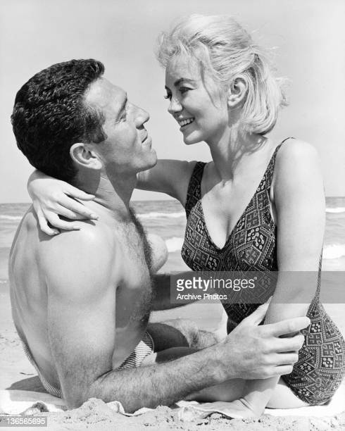 Kieron Moore and Janette Scott embrace each other on the beach in a scene from the film 'Crack In The World' 1965