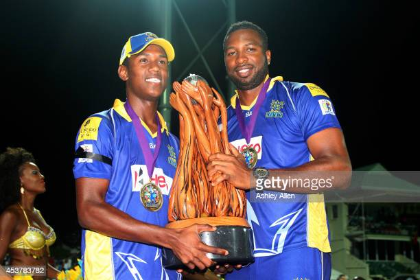 Kieron Pollard and Akeal Hosien of Barbados Tridents pose with the trophy after winning the Limacol Caribbean Premier League 2014 final match between...