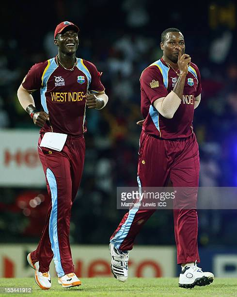 Kieron Pollard of the West Indies celebrates the wicket of Pat Cummins of Australia with Darren Sammy after he was caught by Johnson Charles during...