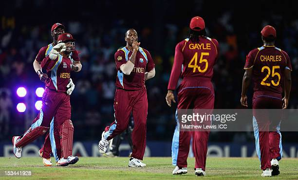 Kieron Pollard of the West Indies celebrates the wicket of Pat Cummins of Australia after he was caught by Johnson Charles during the ICC World...