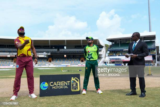 Kieron Pollard of West Indies tosses the coin as Babar Azam and match referee Sir Richie Richardson look on during the 1st T20I between West Indies...