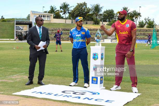 Kieron Pollard of West Indies tosses the coin as Dimuth Karunaratne and match referee Sir Richie Richardson look on during the 1st ODI match between...