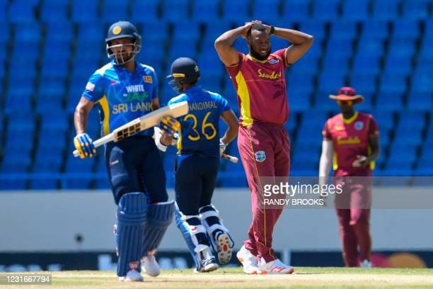 Kieron Pollard of West Indies watches as Dhanushka Gunathilaka and Dinesh Chandimal of Sri Lanka get runs during the 2nd ODI match between West...