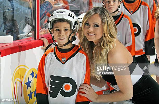 Kiersten Helsel of the Philadelphia Flyers ice girls poses with a member of the Flyers HiFive Club prior to a NHL game against the Calgary Flames on...
