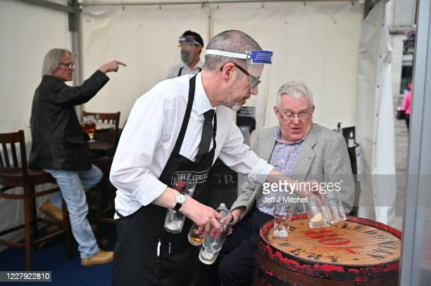Kieth McKenzie wears a shielding face mask as he prepares to close the pub The Grill in Union Street on August 5, 2020 in Aberdeen, Scotland....
