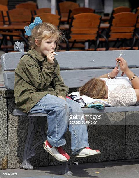 A girl and her mother smoke cigarettes on a bench in the Independence central square of Kiev 06 September 2005 AFP PHOTO/ SERGEI SUPINSKY