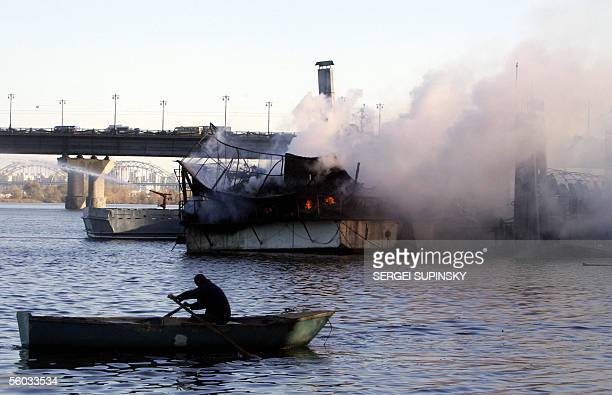 "Man rows a boat to see a fire on a floating restaurant ""Poseidon"" moored to the quay on the Dnieper river in Kiev 30 October, 2005. According to..."