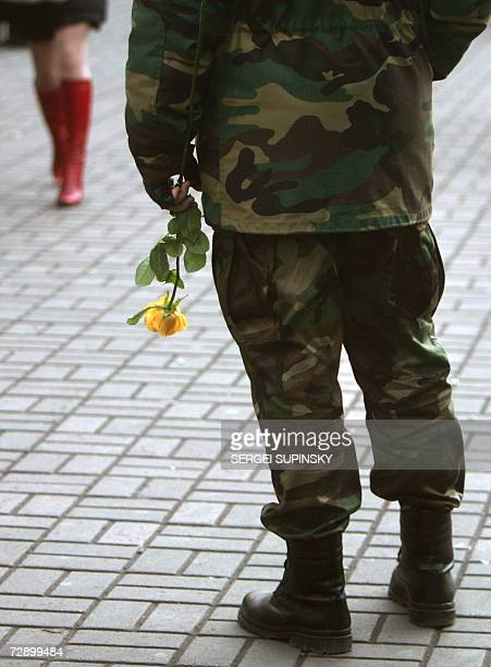 A Ukrainian officer holds a rose as he waits a to meet his girlfriend for a date in the centre of Kiev during a holiday 29 December 2006 AFP PHOTO/...