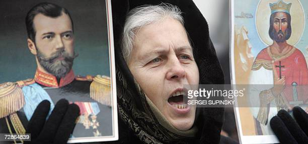 A woman holds an icon and portrait of Russian tsar Nicholas during a proPutin picket in front of the Russian embassy in Kiev 21 December 2006...