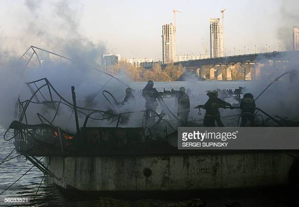 """Firemen extinguish a fire on a floating restaurant """"Poseidon"""" moored to the quay on the Dnieper river in Kiev 30 October, 2005. According to..."""