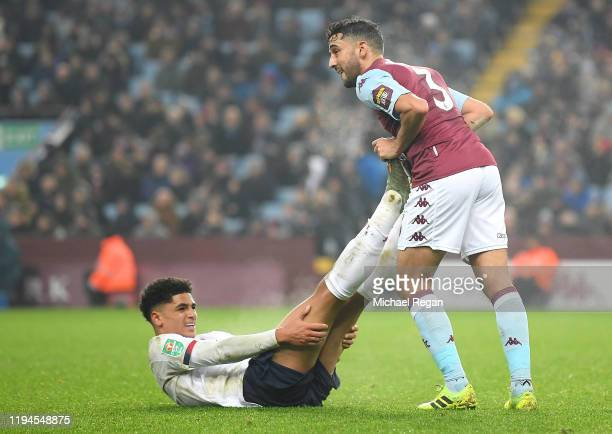 Ki-Jana Hoever of Liverpool is assisted with an injury from Neil Taylor of Aston Villa during the Carabao Cup Quarter Final match between Aston Villa...