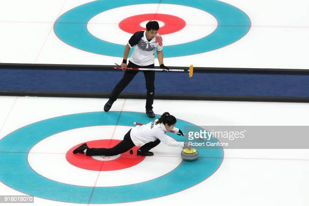 Kijeong Lee and Hyeji Jang of Korea deliver a stone against Becca Hamilton and Matt Hamilton of the United States during the Curling Mixed Doubles...