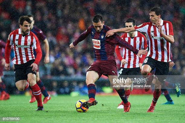 Kike Garcia of SD Eibar being followed by Benat Etxebarria bf and Ander Iturraspe of Athletic Club during the La Liga match between Athletic Club and...