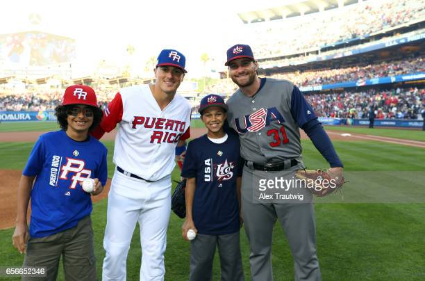Kike Hernandez of Team Puerto Rico and Daniel Murphy of Team USA pose with young fans participating in the cermonial first pitch before Game 3 of the...