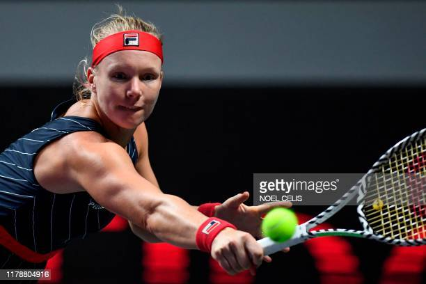 Kiki Bertens of the Netherlands hits a return against Ashleigh Barty of Australia during their women's singles match at the WTA Finals tennis...