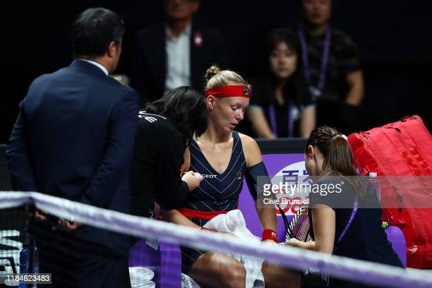 Kiki Bertens of the Netherlands is attended to by tournament and medical staff during her Women's Singles match against Belinda Bencic of Switzerland...