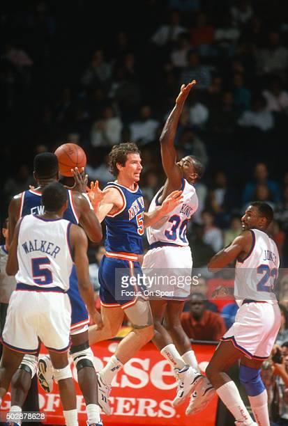Kiki Vandeweghe of the New York Knicks passes the ball away from Bernard King of the Washington Bullets during an NBA basketball game circa 1991 at...