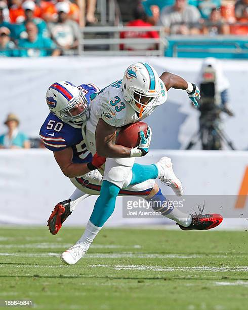 Kiko Alonso of the Buffalo Bills tackles Daniel Thomas of the Miami Dolphins as he runs with the ball on October 20, 2013 at Sun Life Stadium in...