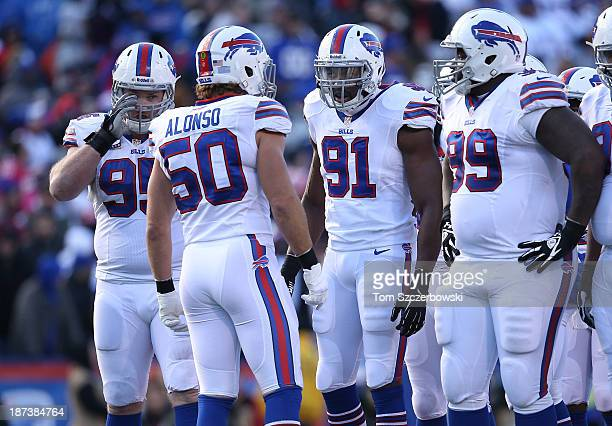 Kiko Alonso of the Buffalo Bills talks to Manny Lawson and Kyle Williams and Marcell Dareus during NFL game action against the Kansas City Chiefs at...