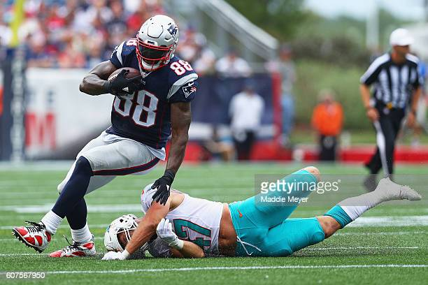 Kiko Alonso of the Miami Dolphins attempts to tackle Martellus Bennett of the New England Patriots during the second half at Gillette Stadium on...