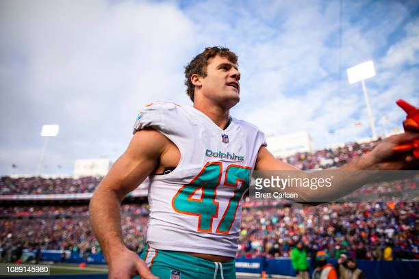 Kiko Alonso of the Miami Dolphins interacts with fans as he is escorted off the field following his ejection during the third quarter against the...