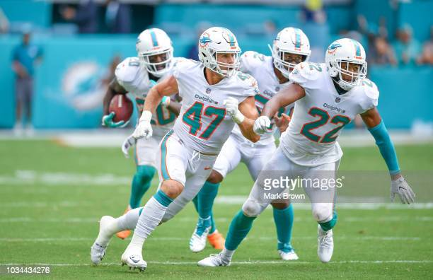 Kiko Alonso, T.J. McDonald, and Raekwon McMillan of the Miami Dolphins look to block for Reshad Jones after intercepting the ball during the game...