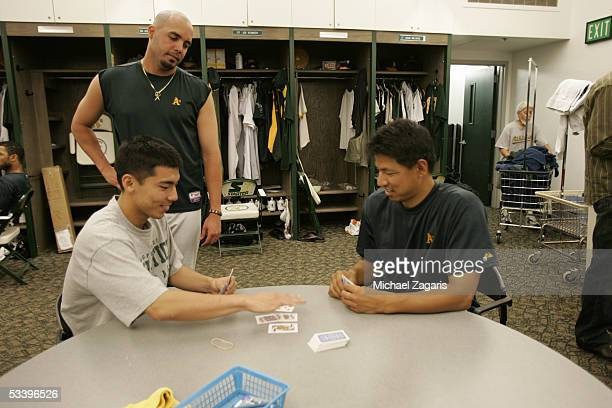 Kiko Calero looks on as Keiichi Yabu of the Oakland Athletics plays cards in the clubhouse before the game against the Cleveland Indians at McAfee...