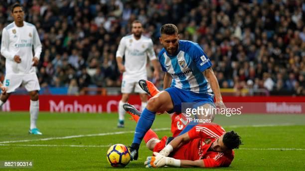 Kiko Casilla of Real Madrid and Borja Baston of Malaga battle for the ball during the La Liga match between Real Madrid and Malaga at Estadio...