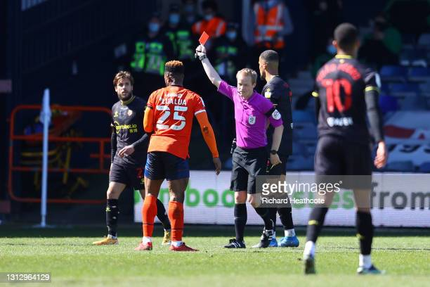 Kiko Femenia of Watford FC is shown a second yellow, followed by a red card and sent off by referee Gavin Ward during the Sky Bet Championship match...