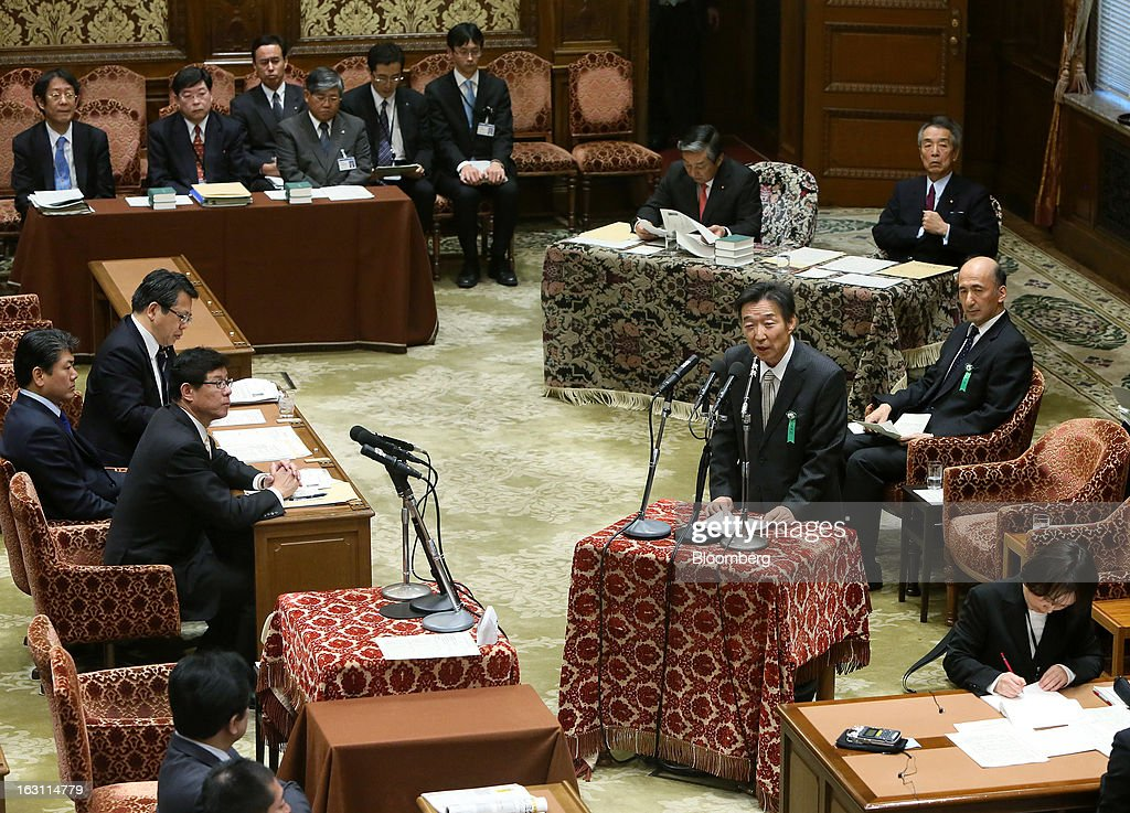 Kikuo Iwata, professor of economics at Gakushuin University and nominee for deputy governor of the Bank of Japan (BOJ), center standing, speaks as Hiroshi Nakaso, assistant governor and executive director of the BOJ and nominee for second deputy governor of the BOJ, center right seated, looks on during a confirmation hearing at the lower house of Parliament in Tokyo, Japan, on Tuesday, March 5, 2013. The Bank of Japan should buy longer-term bonds to help it achieve a 2 percent inflation target, said Iwata. Photographer: Haruyoshi Yamaguchi/Bloomberg via Getty Images