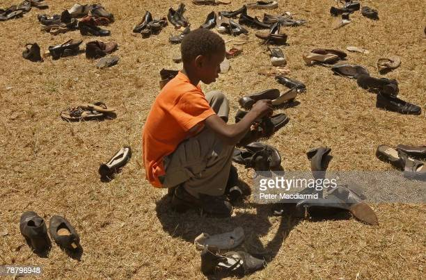 Kikuyu boy looks for shoes donated by local people at the Nakuru show ground on January 7 2008 in Nakuru Kenya Local volunteers and charities are...
